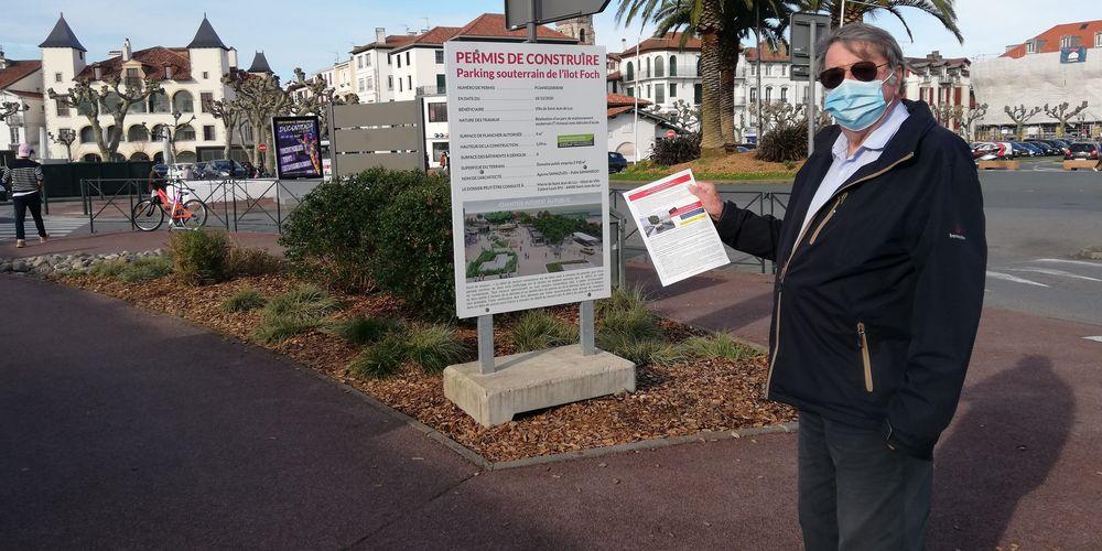 Francois Xavier Letamendia présentant la pétition contre le projet de parking souterrain de l'îlot Foch à Saint-Jean-de-Luz devant l'affichage du permis de construire de ce dernier